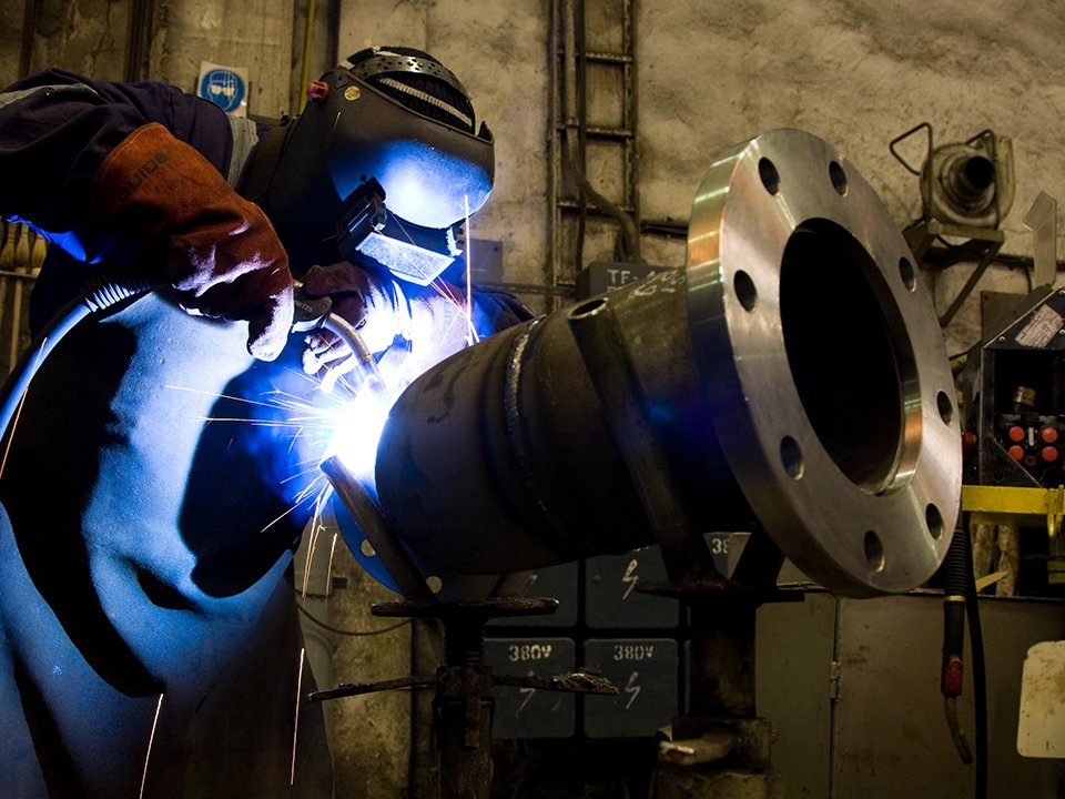 An experienced metal fabrication worker welding a large metal part for a customer.