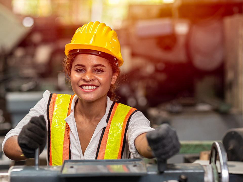Female metal fabrication worker smiles while using equipment